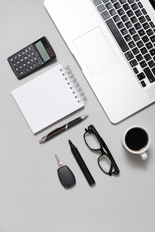 High angle view of laptop; calculator; blank notepad; eyeglasses; and coffee cup with key on gray backdrop