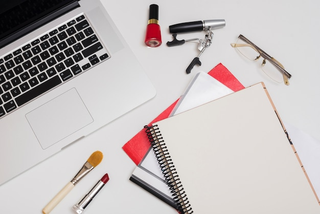 High angle view of laptop; cosmetic products; folders and eyeglass on office desk