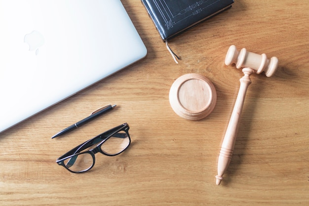 High angle view of laptop; spectacles; gavel and pen on wooden background on wooden desk