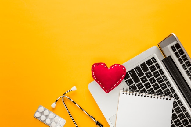 High angle view of laptop; spiral notepad; blister packed medicine; stethoscope; stitched heart shape above yellow backdrop