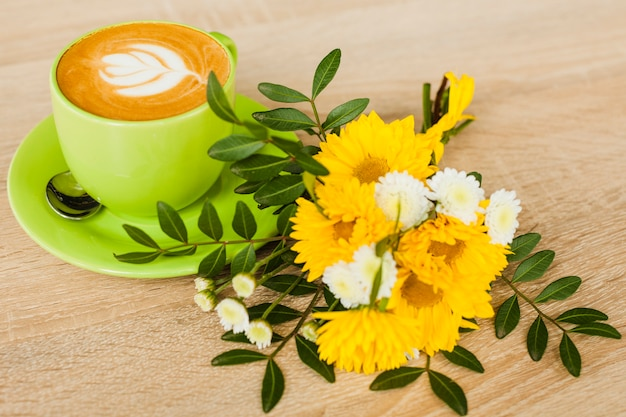High angle view of latte art coffee cup with fresh flower over wooden textured backdrop
