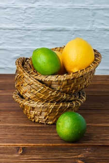 High angle view lemons in baskets on wooden surface. vertical space for text
