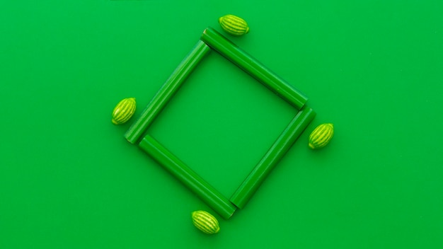 High angle view of licorice and lemon candies on green background