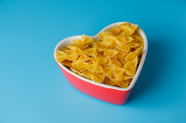 High angle view macaroni pasta in heart shaped bowl