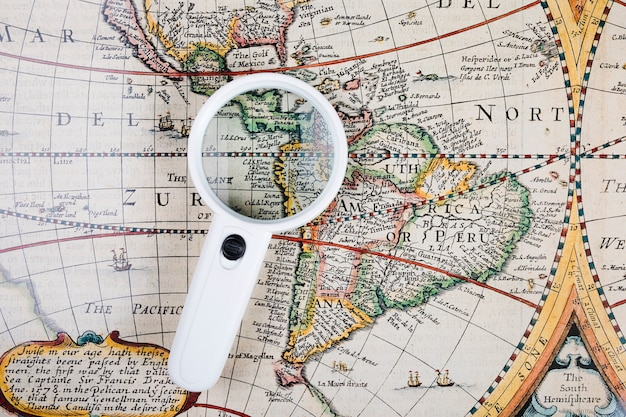High angle view of magnifying glass on old world map