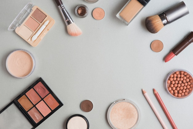 High angle view of make up kits forming circular shape on white backdrop