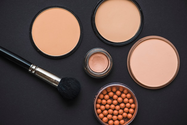 High angle view of make up products with brush on black backdrop