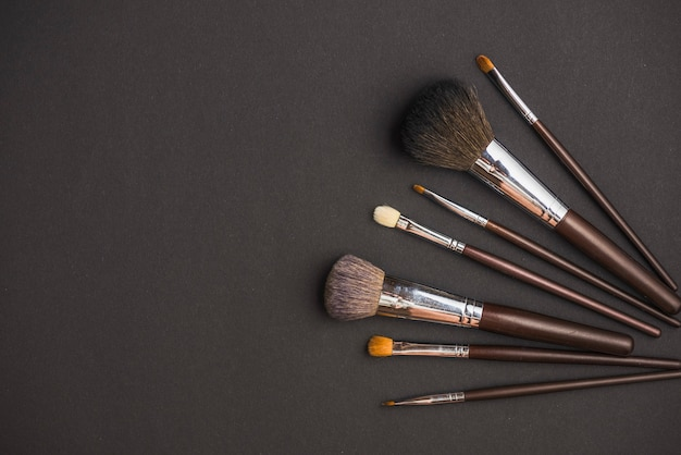High angle view of makeup brushes on black surface