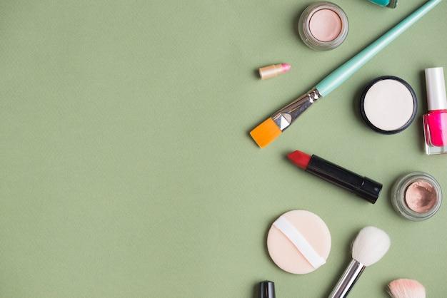 High angle view of makeup kit on green backdrop