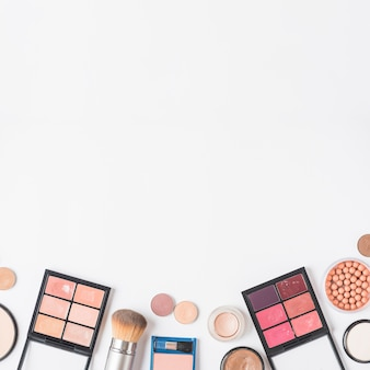 High angle view of makeup kits at the bottom of white backdrop