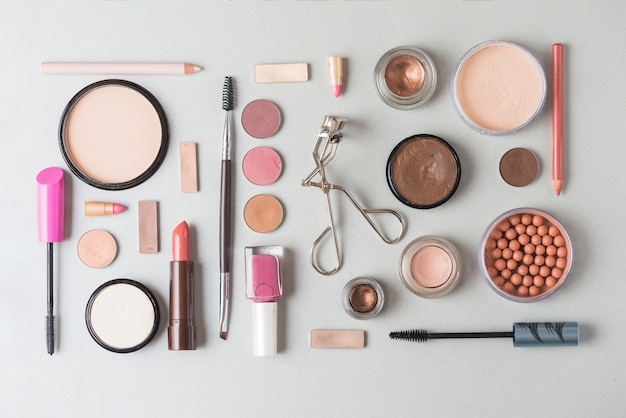 High angle view of makeup products arranged in rectangular shape on white background