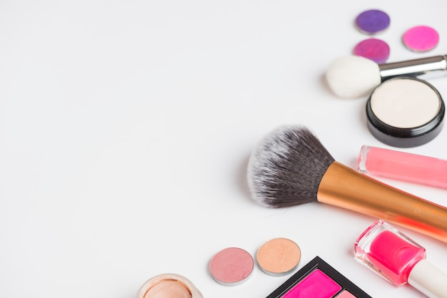 High angle view of makeup products on white backdrop