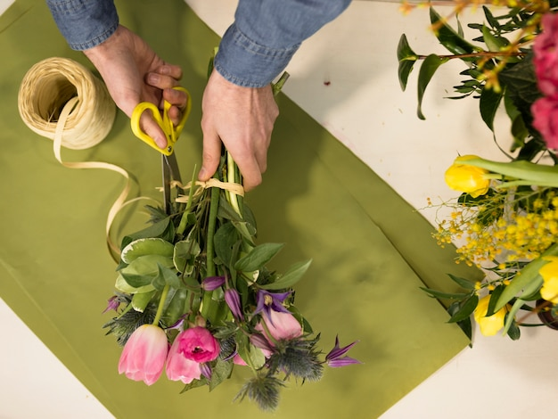 High angle view of male florist hand creating the flower bouquet