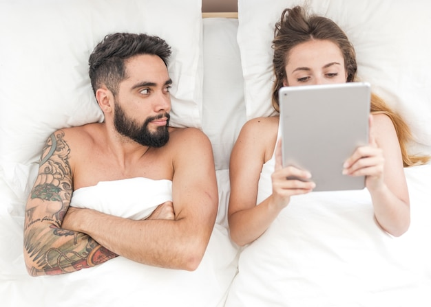 High angle view of man looking at his wife using digital tablet on bed