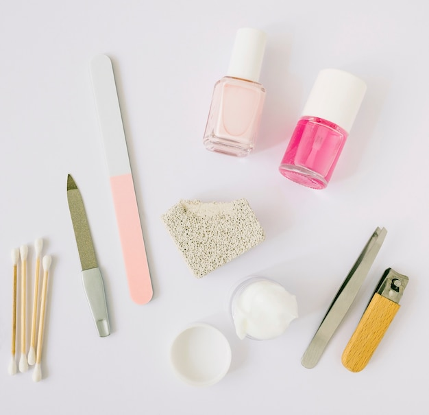 High angle view of manicure tools and products on white backdrop