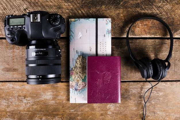 High angle view of map, passport, headphone and dslr camera on wooden background