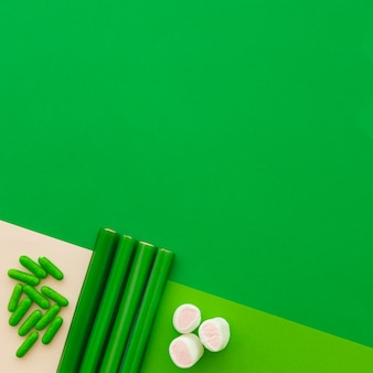 High angle view of marshmallow, capsule and licorice candies on green backdrop