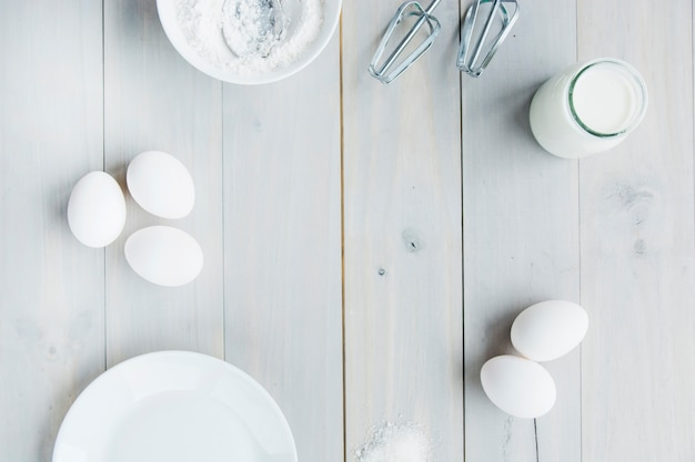 High angle view of milk; flour; whisk and eggs on wooden plank