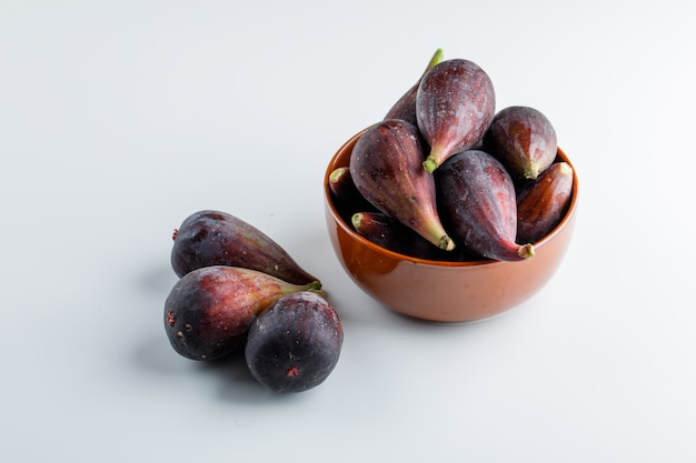 High angle view mission figs in bowl and nearby on white wall. horizontal