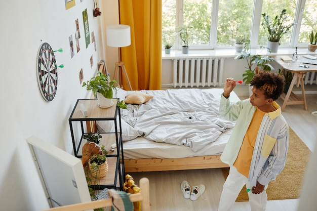 High angle view at mixed-race teenage boy throwing darts in cozy room interior, copy space