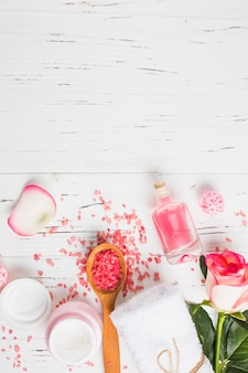 High angle view of moisturizing cream; oil bottle; flower; salt and towel on wooden background