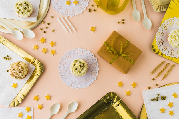 High angle view of muffins and gifts on decorative colored background