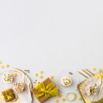 High angle view of muffins and gifts at the edge of white backdrop