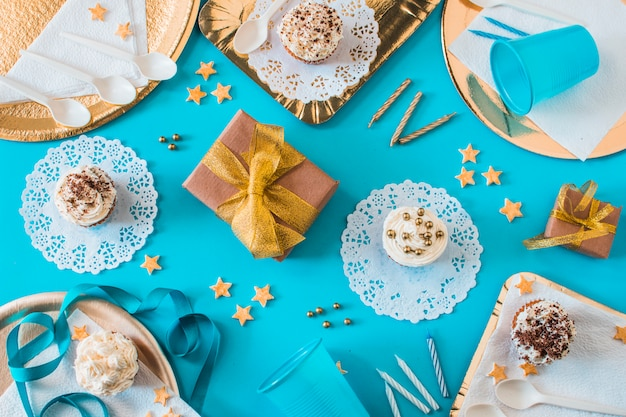 High angle view of muffins with gifts and candles on blue background