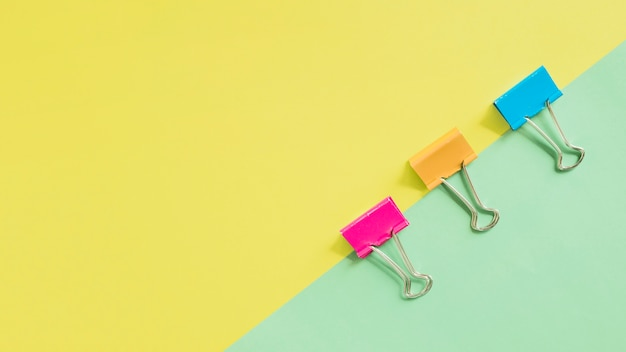 High angle view of multi colored bulldog clips on dual background