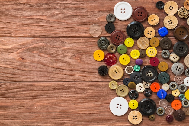 High angle view of multi colored buttons on wooden plank