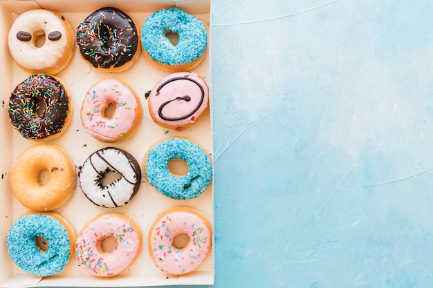 High angle view of multi colored fresh donuts in box on blue background