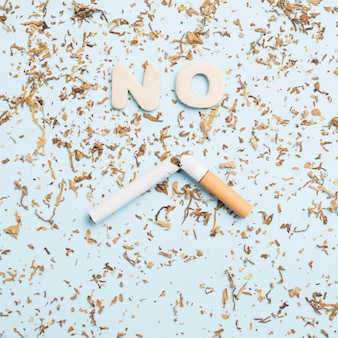 High angle view of no word and broken cigarette with tobacco over blue background