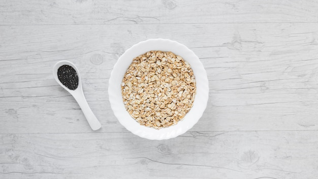 High angle view of oats and chia seeds over wooden table