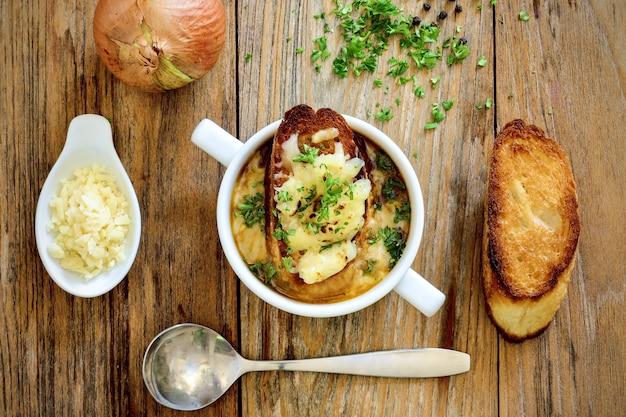 ライトの下でテーブルの上のスープとグリルしたパンのボウルの高角度のビュー