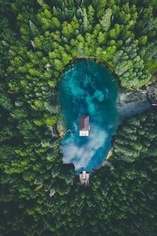 Высокий угол обзора здания в озере в окружении лесов под пасмурным небом