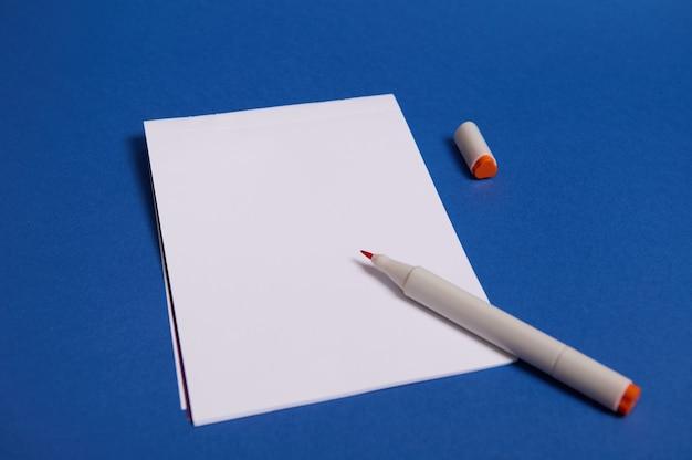 Высокий угол обзора композиции с акварельным маркером или фломастерами на белом чистом листе бумаги с копией пространства для текста, изолированного на синем фоне.