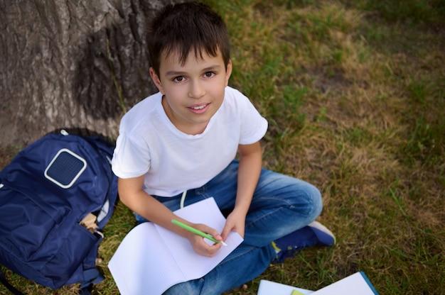 学校での初日の後、かわいい男の子、小学生の小学生、ワークブックにカメラの書き込みを見上げて、屋外で宿題をしている高角度のビュー。学校に戻る。愛らしい生徒の肖像画