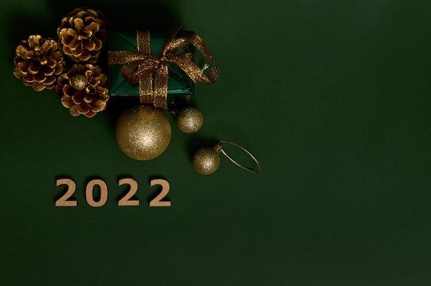 Подарок в зеленой оберточной бумаге под высоким углом с золотым бантом, сосновыми шишками, деревянными цифрами, символизирующими 2022 год, и золотыми елочными игрушками, выложенными на темном фоне. скопируйте место для рекламы