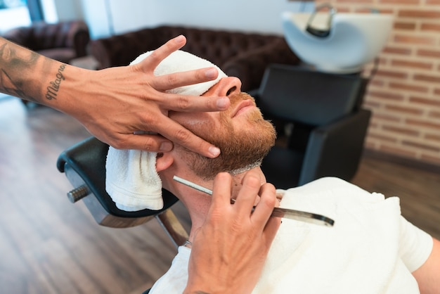 칼날로 고객의 수염을 면도하는 문신이 있는 미용사의 높은 각도