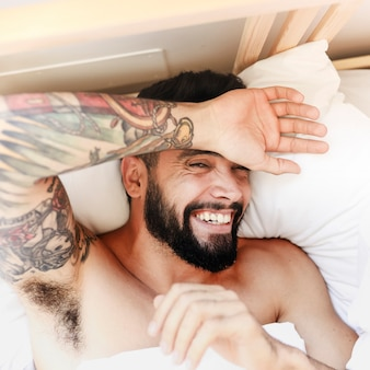 High angle view of a happy man lying on bed