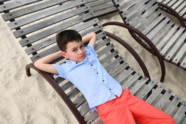 Высокий угол обзора счастливого подростка, лежа на деревянном шезлонге. красивый ребенок отдыхает на шезлонге во время летних загородных каникул. дети на каникулах