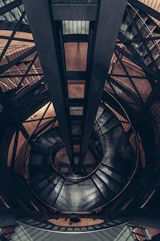 らせん階段のある暗い古い建物のリフトシャフトの高角度ビュー