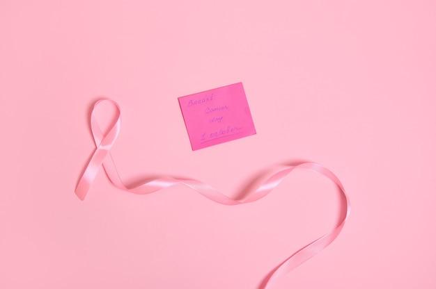 끝이 없는 긴 분홍색 리본의 높은 각도 보기 및 복사 공간이 있는 분홍색 배경에 격리된 10월 1일 유방암 인식이 있는 종이 메모. 플랫 레이