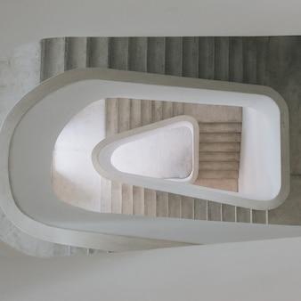 Высокий угол обзора современной винтовой лестницы на выставке под светом