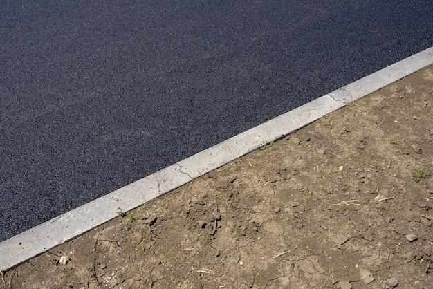햇빛 아래 도로에 새로 놓인 아스팔트의 높은 각도보기
