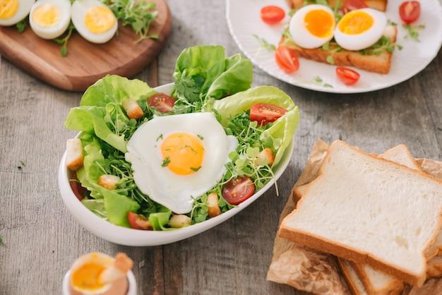 木製のテーブルの上に白いプレートで提供されるゆで卵のスライスと栄養価の高い野菜サラダの高角度ビュー