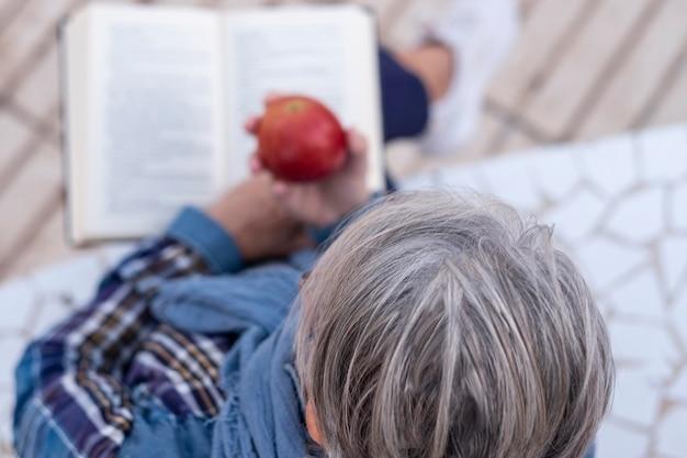 Высокий угол обзора пожилой женщины с седыми волосами, читающей книгу с яблоком в руках. здоровый образ жизни пенсионеров.