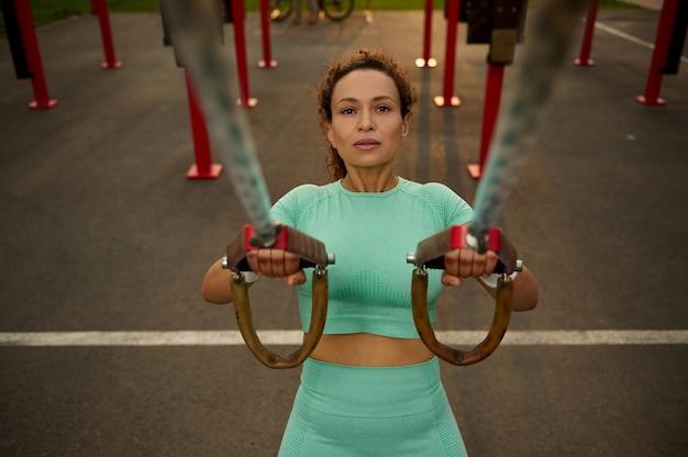 スポーツグラウンドで屋外クロストレーニングを実行しながらサスペンションストラップで腕のエクササイズをしているスポーティな決定的な中年のアフリカ系アメリカ人、混血の女性の高角度のビュー