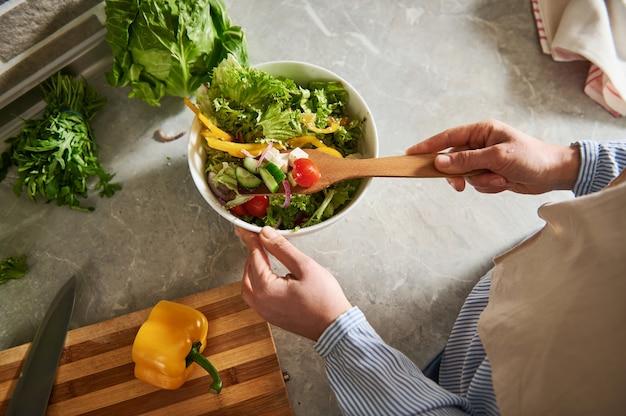식탁에 나무로되는 숟가락으로 샐러드를 혼합하는 여자의 높은 각도보기.
