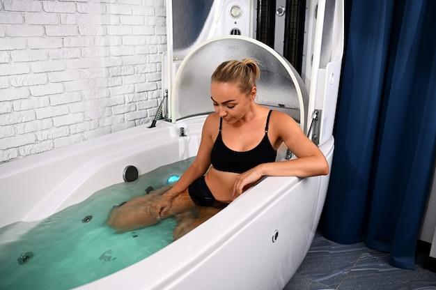 Высокий угол обзора женщины с идеальным телом, получающей неинвазивную антивозрастную антицеллюлитную процедуру в ванне открытой спа-капсулы